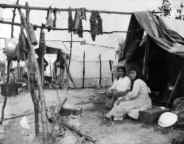 ALASKA: ESKIMOS, c1916.   Two Eskimo women sitting outside their tent, with fish hanging to dry above them, Nome, Alaska. Photograph, c1916
