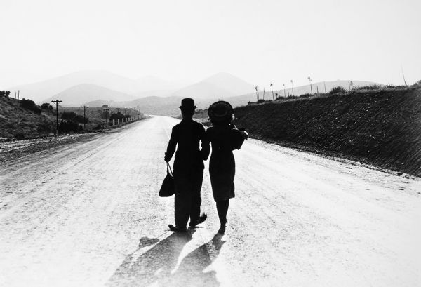 CHAPLIN: MODERN TIMES, 1936.  Charlie Chaplin and Paulette Goddard in the final scene from the film, 'Modern Times,' 1936