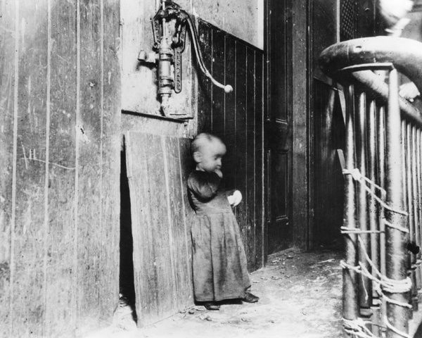 NYC: TENEMENT, c1890.   A child standing in the hallway of a tenement building. Photograph by Jacob Riis, c1890
