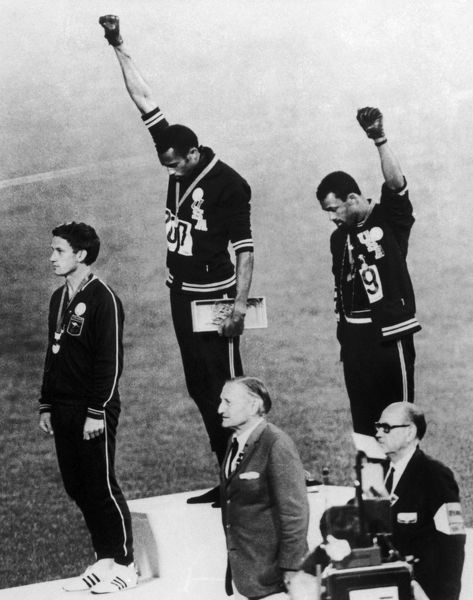 OLYMPIC GAMES, 1968. American runners Tommie Smith (center) and John Carlos (right) showing the Black Power salute during the medal ceremonies at the Olympic Games in Mexico City. Australian Peter Norman (left) wears an OPHR badge in solidarity. Photograph, 1968