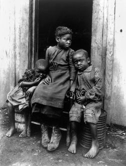 AFRICAN AMERICAN CHILDREN. Three African American children seated in a doorway