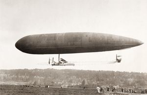 AIRSHIP. An airship flying over an airfield. Early 20th century photograph.