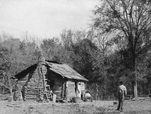 ALABAMA: LOG CABIN, c1890. Three African Americans outside a log cabin in Mt. Meigs