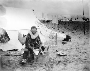 ALASKA: ESKIMO, c1906. An Inuit man doing laundry in tub outside his tent, with
