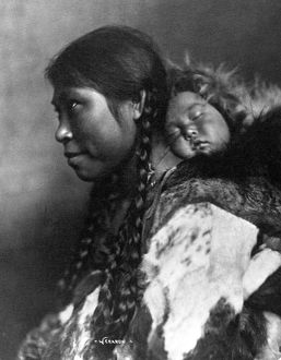 ALASKA: ESKIMOS, c1905. A mother carrying her sleeping child on her back, Nome, Alaska