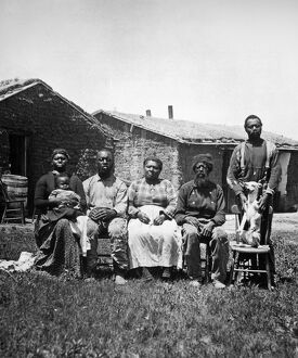 BLACK HOMESTEADERS. A black family photographed in 1887 before their homestead