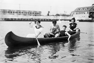 CANOE, c1910. Two women paddling a canoe with two men, one holding a camera. Photograph