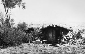 COLORADO: DUGOUT HOME. A frontiersman seated outside his dugout cabin in Grand County