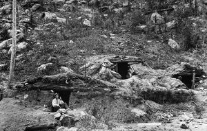 COLORADO: DUGOUT HOME. A man seated outside a dugout cabin at the side of a hill