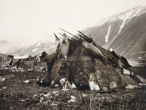 ESKIMO DWELLING, c1899. A group of three Inuits sitting in front of their house