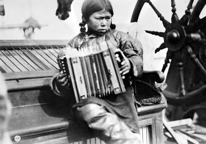 ESKIMO GIRL, c1913. A young Eskimo girl sitting on the deck of a boat playing the