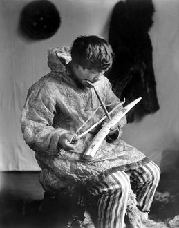 ESKIMO IVORY CARVER, c1912. A seated Eskimo man working as an ivory carver, Arctic region