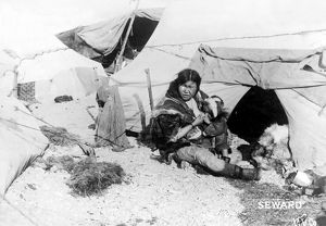 ESKIMO WOMAN AND CHILD. An Eskimo woman sitting outside a tent breast-feeding her baby