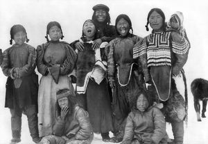 ESKIMOS, c1913. A group of nine Eskimos, including a woman with a baby on her back