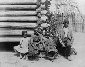 GEORGIA: CHILDREN, c1886. A group of African American children outside a log building