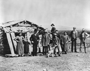 IDAHO: SETTLERS, c1882. A group of settlers standing outside a log cabin in American Falls