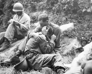 KOREAN WAR, 1950. An American infantryman comforted by a comrade upon learning of