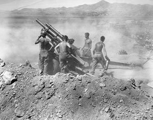 KOREAN WAR: ARTILLERY. U.S. artillerymen firing a 105mm howitzer on North Korean