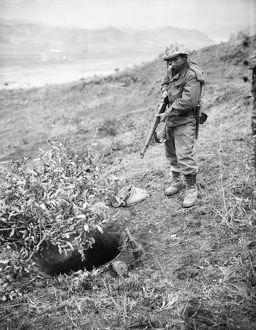 KOREAN WAR: FOXHOLE, 1951. A U.S. Marine on the central Korean front checks a foxhole