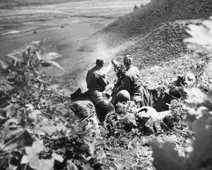 KOREAN WAR: MACHINE GUN. American soldiers man a machine gun on a hilltop position