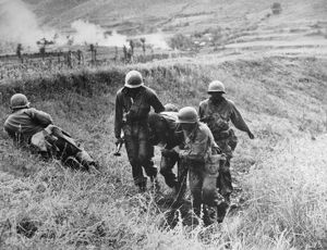 KOREAN WAR: WOUNDED, 1950. U.S. Army soldiers of the 9th Infantry aiding a wounded comrade