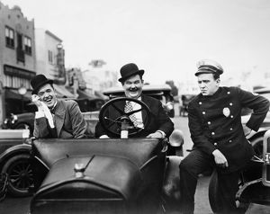 LAUREL AND HARDY, 1928. Stan Laurel, left, and Oliver Hardy with a police officer