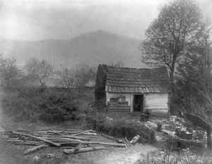 LOG CABIN, c1900. A man sitting in front of a small log cabin on a Sunday morning