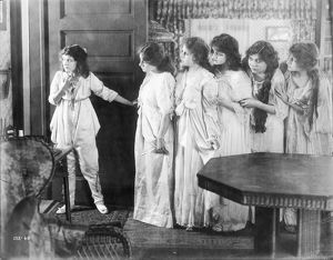 Marguerite Clark and other cast members in a scene from the silent film, 1916; American.