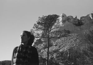 MOUNT RUSHMORE, c1936. A woman posing in front of the construction of Mount Rushmore