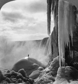 NIAGARA FALLS: FROZEN. Person standing on top of ice mound at Niagara Falls in winter