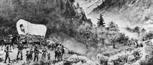 OREGON TRAIL: EMIGRANTS. An emigrant wagon train on the Oregon Trail passing through