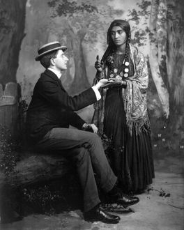 PALM-READING, c1910. A staged depiction of a Gypsy woman reading a man's palm