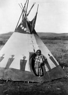 PIEGAN GIRL, c1910. The daughter of a Piegan Blackfoot chief, standing at her tepee