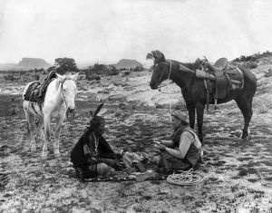 PLAYING CARDS, c1915. A cowboy and a Native American man seated on a blanket