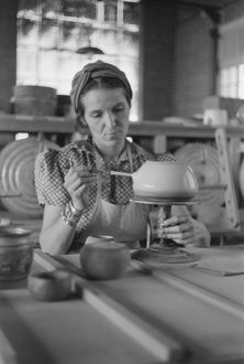 POTTERY MAKING, 1940. A woman working at a pottery wheel, possibly at the Indian