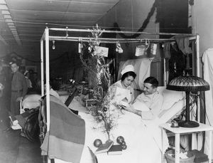 RED CROSS: CHRISTMAS. An American Red Cross nurse alongside a wounded soldier during