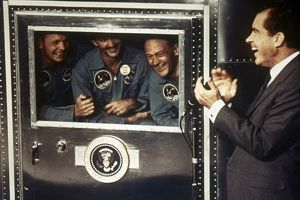 SPACE: APOLLO 11. President Richard M. Nixon applauds astronauts Neil Armstrong, Michael Collins