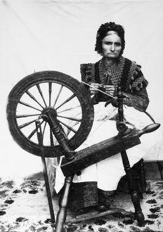 SPINNING WHEEL. An American woman spinning yarn. Photograph, 19th century