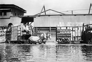 ST. LOUIS: FLOOD, 1909. A horse-drawn wagon at the flooded levee in St. Louis, Missouri