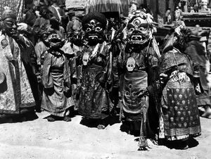 Tibetan monks wearing masks, each symbolizing a mental defilement