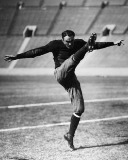 An unidentified American football player kicking the ball, early 20th century